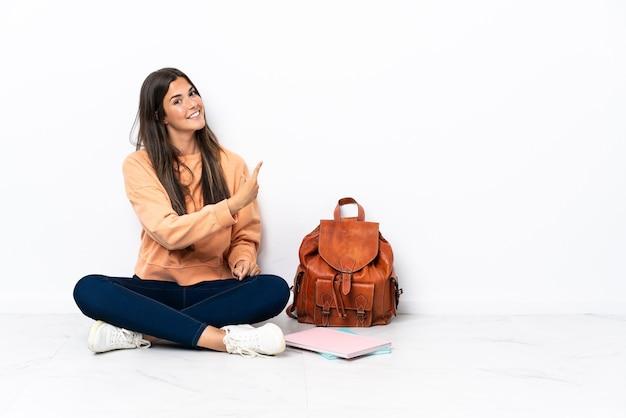Donna brasiliana del giovane studente che si siede sul pavimento che indica indietro