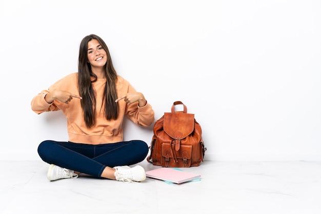 Giovane studentessa brasiliana seduta sul pavimento orgogliosa e soddisfatta