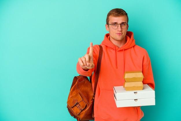 Giovane studente caucasico che tiene hamburger e pizze isolati su sfondo blu che mostra il numero uno con il dito.