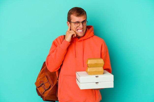 Giovane studente caucasico che tiene hamburger e pizze isolate su blu che copre le orecchie con le mani.