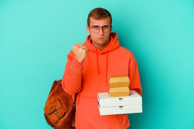 Uomo caucasico del giovane studente che tiene hamburger e pizze isolati sul pugno blu che mostra, espressione facciale aggressiva.