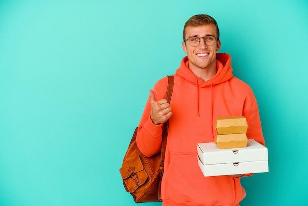 Giovane studente caucasico che tiene hamburger e pizze isolati su blu sorridente e alzando il pollice thumb