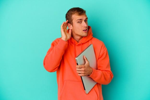 Uomo caucasico del giovane studente che tiene un computer portatile isolato su fondo blu che prova ad ascoltare un gossip.