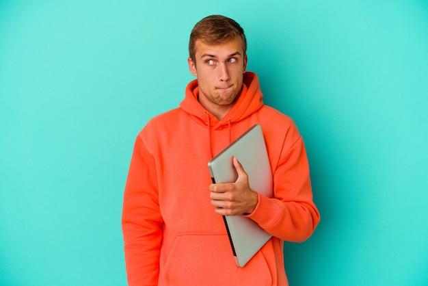 L'uomo caucasico del giovane studente che tiene un computer portatile isolato sulla parete blu è confuso, si sente dubbioso e insicuro.