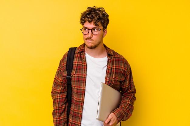 Giovane studente caucasico che tiene in mano un laptop isolato su sfondo giallo confuso, si sente dubbioso e incerto.
