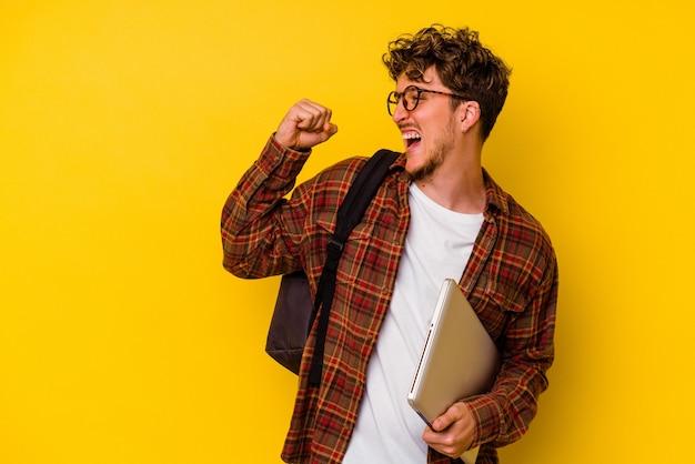 Uomo caucasico del giovane studente che tiene un computer portatile isolato su fondo giallo che alza il pugno dopo una vittoria, concetto del vincitore.