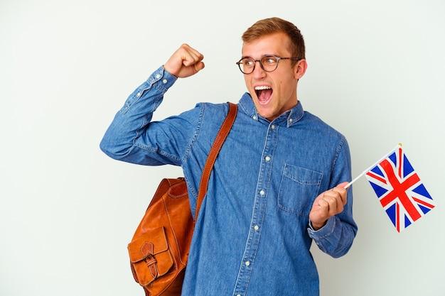 Uomo caucasico del giovane studente che studia inglese isolato su fondo bianco che alza il pugno dopo una vittoria, concetto del vincitore.