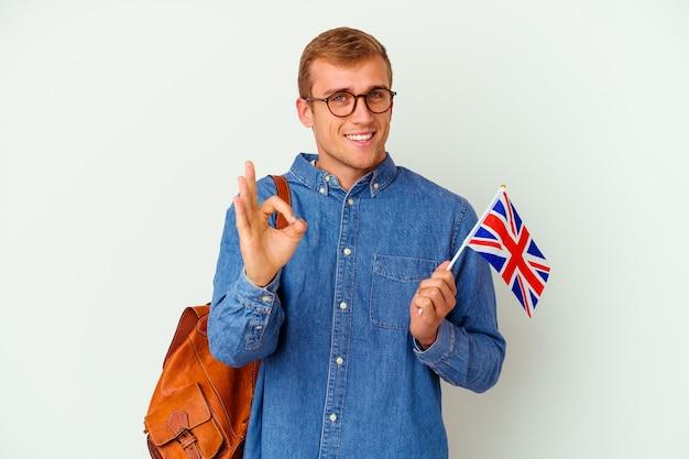 Uomo caucasico del giovane studente che studia inglese isolato su bianco allegro e sicuro che mostra gesto giusto.