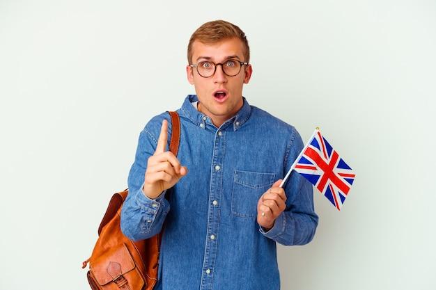 Uomo caucasico del giovane studente che studia inglese isolato su bianco che ha un'idea, concetto di ispirazione.