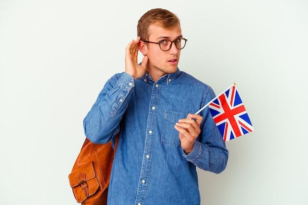 Uomo caucasico del giovane studente che studia inglese isolato su bianco che prova ad ascoltare un pettegolezzo.