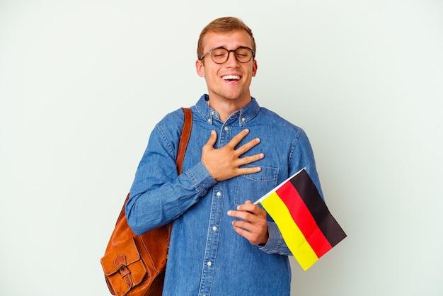 Giovane studente caucasico che studia tedesco isolato su sfondo bianco ride forte tenendo la mano sul petto.