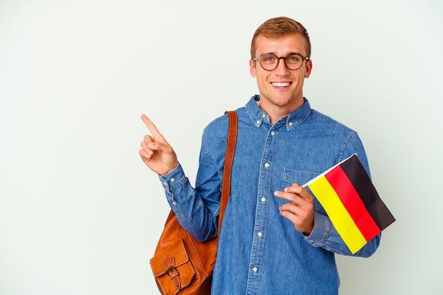 Uomo caucasico giovane studente che studia tedesco isolato su bianco sorridendo e indicando da parte, mostrando qualcosa in uno spazio vuoto.