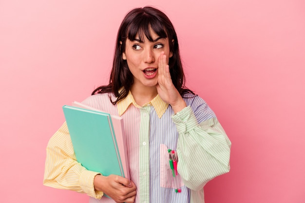 Giovane studentessa caucasica che tiene libri isolati su sfondo rosa sta dicendo una notizia segreta di frenata calda e sta guardando da parte