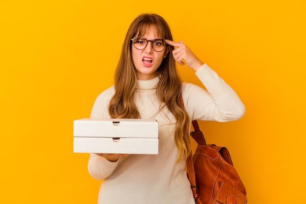 Donna caucasica del giovane studente che tiene le pizze sopra la parete isolata che mostra un gesto di delusione con l'indice.
