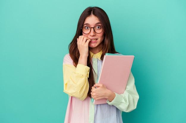 Giovane studentessa caucasica isolata su sfondo blu che si morde le unghie, nervosa e molto ansiosa.