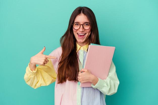 Giovane studentessa caucasica isolata su sfondo blu persona che indica a mano uno spazio copia camicia, orgogliosa e sicura di sé