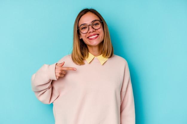 Donna caucasica del giovane studente isolata sulla persona della parete blu che indica a mano uno spazio della copia della camicia, orgoglioso e fiducioso