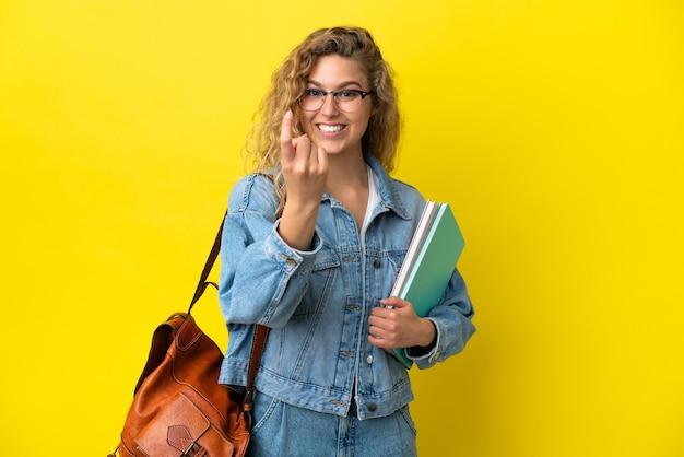 Donna caucasica del giovane studente isolata su fondo giallo che fa il gesto venente