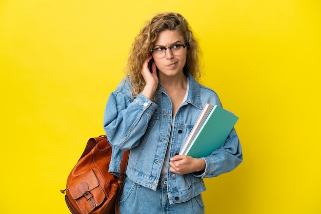 Giovane studentessa caucasica isolata su sfondo giallo frustrata e che copre le orecchie