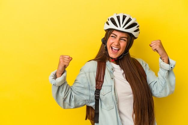 Giovane studentessa caucasica che indossa un casco da bici isolato su sfondo giallo alzando il pugno dopo una vittoria, concetto di vincitore.