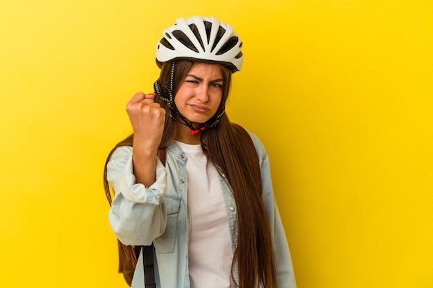 Giovane studentessa caucasica che indossa un casco da bici isolato su sfondo giallo che mostra il pugno alla telecamera, espressione facciale aggressiva.