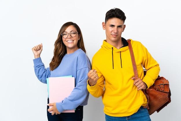 Coppia giovane studente su bianco che celebra una vittoria