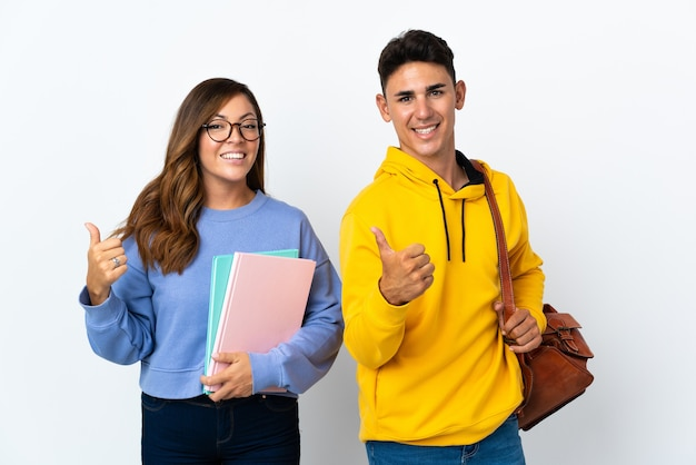 Coppia giovane studente su bianco dando un pollice in alto gesto con entrambe le mani e sorridente