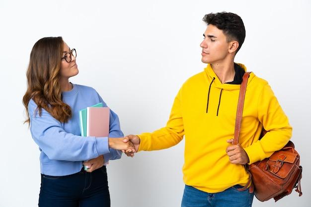 Coppia giovane studente su handshaking bianco dopo un buon affare