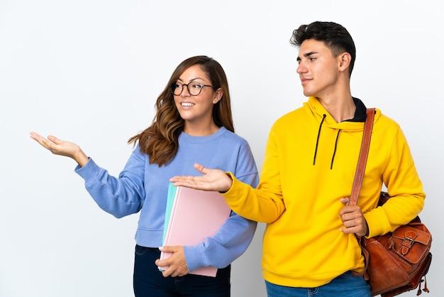 Coppia giovane studente su bianco che punta indietro e che presenta un prodotto