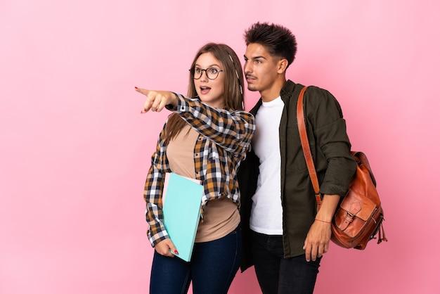 Coppia giovane studente su bianco che punta al lato per presentare un prodotto