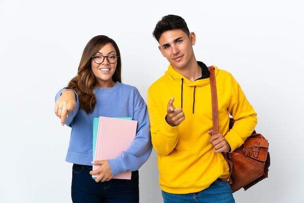 Giovane coppia di studenti su bianco punta il dito contro di te con un'espressione sicura