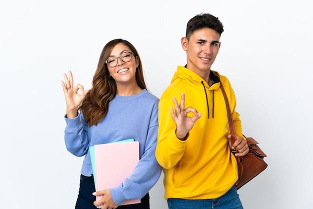 Coppia giovane studente su bianco che mostra un segno ok con le dita