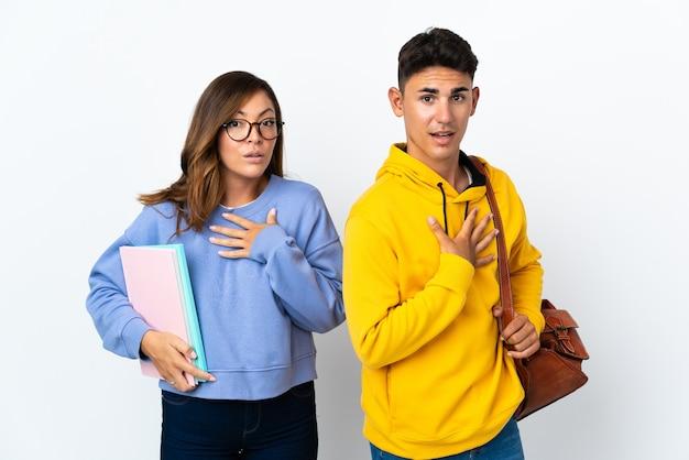 Coppia giovane studente su bianco sorpreso e scioccato mentre guarda a destra
