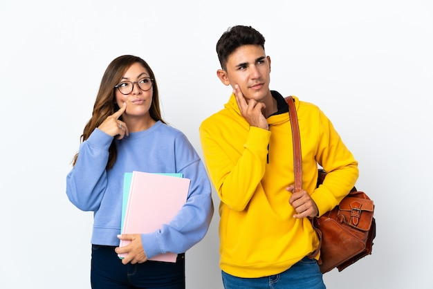 Giovani coppie dell'allievo su bianco che pensa un'idea mentre osserva in su