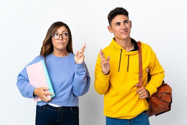 Coppia giovane studente su bianco con le dita incrociate e che desiderano il meglio