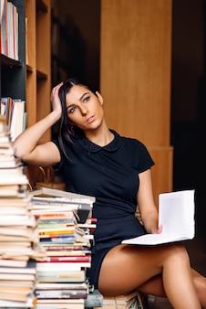 Giovane ragazza dello studente che legge il libro che si siede sul mucchio dei libri alla vecchia biblioteca
