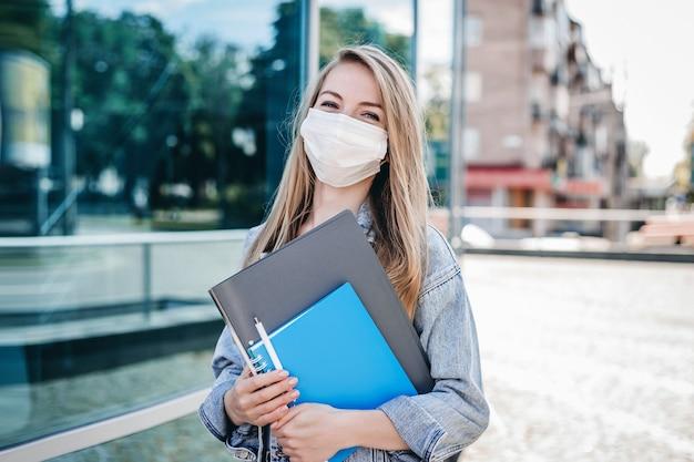 Una giovane studentessa in una mascherina chirurgica in piedi dietro un edificio universitario di vetro