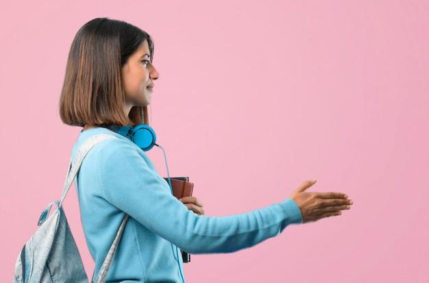 Giovane ragazza dell'allievo con il handshake blu delle cuffie e del maglione dopo il buon affare