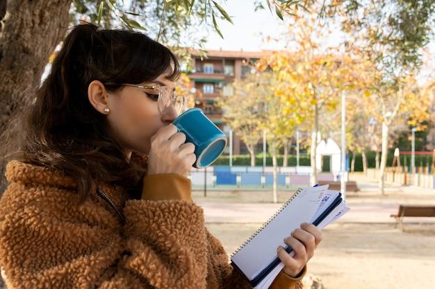 Ragazza giovane studente con gli occhiali che consulta la sua agenda al parco.