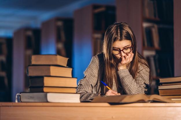 Giovane studente in bicchieri preparando per l'esame. ragazza di sera si siede a un tavolo in biblioteca con una pila di libri