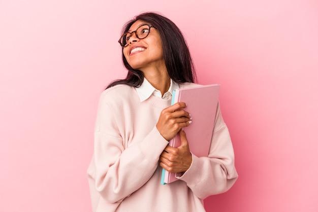 Giovane studentessa latina isolata su sfondo rosa che sogna di raggiungere obiettivi e scopi