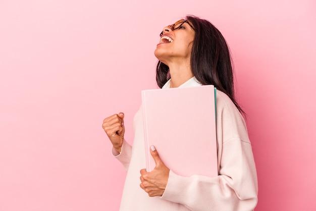 Giovane studentessa latina isolata su sfondo rosa che alza il pugno dopo una vittoria, concetto di vincitore.