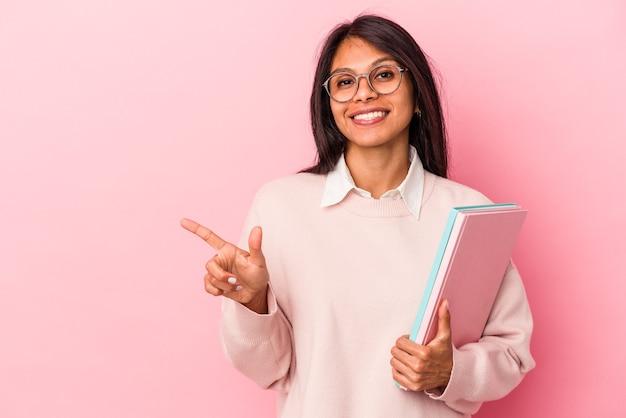Giovane studentessa latina isolata su sfondo rosa sorridente e puntata da parte, mostrando qualcosa in uno spazio vuoto.