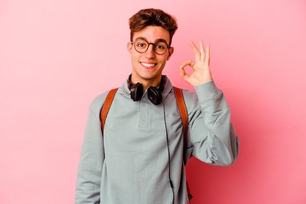 Uomo giovane studente isolato su sfondo rosa allegro e fiducioso che mostra gesto giusto.