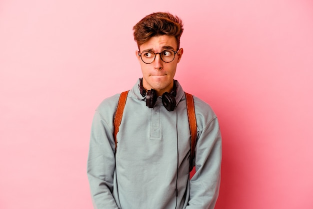 Uomo giovane studente isolato su sfondo rosa confuso, si sente dubbioso e insicuro.