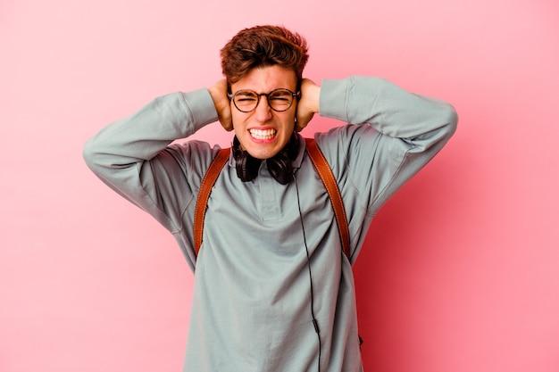 Uomo giovane studente isolato su sfondo rosa che copre le orecchie con le mani cercando di non sentire un suono troppo forte.