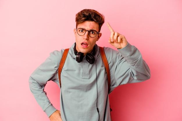 Uomo giovane studente isolato su sfondo rosa con un'idea, concetto di ispirazione.