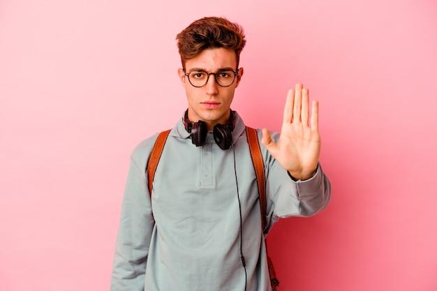 Uomo giovane studente isolato su sfondo rosa in piedi con la mano tesa che mostra il segnale di stop, impedendoti.