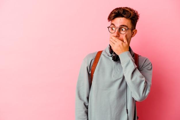 Uomo giovane studente isolato su sfondo rosa premuroso cercando di uno spazio di copia che copre la bocca con la mano.