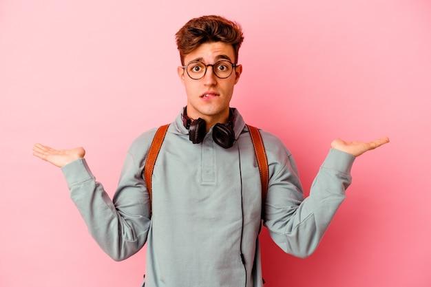Giovane studente uomo isolato sulla parete rosa confuso e dubbioso scrollare le spalle per tenere uno spazio di copia.